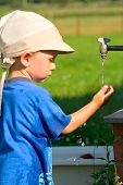stock photo of water jet  - Little boy plays with a jet of water at the tap in the village