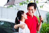 pic of politeness  - Asian man with umbrella walking woman in rain from car door to house - JPG