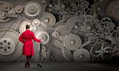 stock photo of mechanical engineering  - Young woman in red coat fixing mechanism with wrench - JPG