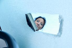 stock photo of scrape  - Woman scraping ice from a windshield - JPG