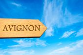 picture of avignon  - Wooden arrow sign pointing destination AVIGNON FRANCE against clear blue sky with copy space available - JPG