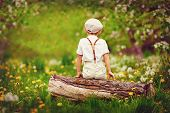 image of rear-end  - cute little boy sitting on wooden log in spring garden - JPG