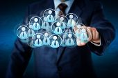foto of human resource management  - Torso of a manager in blue business suit selecting white color worker icons in a virtual cloud shaped of many office worker symbols - JPG