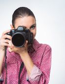 stock photo of shoot out  - Female photographer shooting with a dslr camera on white background - JPG