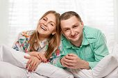 picture of laying-in-bed  - Happy smiling couple laying laughing in bed - JPG