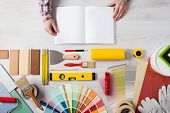 picture of hand tools  - Hands holding DIY training open manual with work tools color swatches and painting rollers at bottom top view - JPG