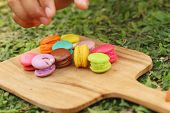 foto of picking tray  - Hand were picked colorful of macaron on a brown tray - JPG