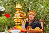 image of curvaceous  - Beautiful Russian girl with a curvaceous rosy and happy sitting at a table with a samovar drying bagels budlikami strawberries in the spring blooming garden bright colors and spring - JPG