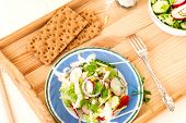 stock photo of chinese parsley  - Spring salad with radishes cucumber Chinese cabbage and red onion closeup in glass bowl on a white wooden background - JPG