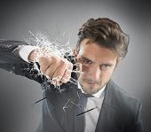 picture of punch  - Determined businessman breaks the glass with punch - JPG