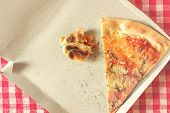 stock photo of lunch box  - Pizza Slice and Fast Food Leftovers in Cardboard Box on Kitchen Table Retro Style Toned Image Selective Focus with Shallow Depth of Field - JPG