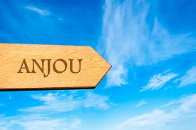 picture of anjou  - Wooden arrow sign pointing destination ANJOU FRANCE against clear blue sky with copy space available - JPG
