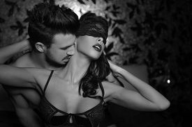 stock photo of bondage  - Sexy playful couple in bed foreplay kissing neck black and white - JPG