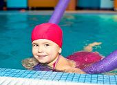 stock photo of cute little girl  - Happy little girl learning to swim with pool noodle - JPG