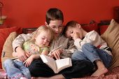 stock photo of storytime  - 3 children at home reading a book together - JPG