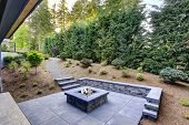 New Modern Home Features A Backyard With Fire Pit poster