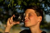 Young Photographer With Retro Film Photo Camera In Garden. The Boy Holds A Camera In His Hands And T poster