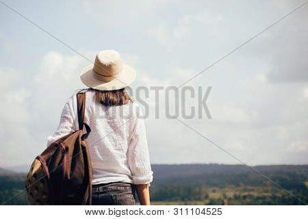 poster of Hipster Girl With Backpack Traveling And Standing On Top Of Sunny Mountain And Looking At Sky And Wo