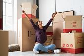 Happy young woman sitting in new apartment and raising arms in joy after moving in. Joyful and excit poster