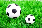 One Big And One Little Soccer Ball On Plastic Grass