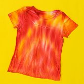 T-shirt Decorated In Tie Dye Style In Yellow And Red Colors On A Yellow Background. Flat Lay. Staini poster