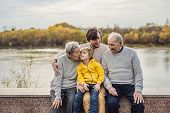 Senior Couple With With Grandson And Great-grandson In The Autumn Park. Great-grandmother, Great-gra poster