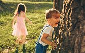 Happy Children Playing Together Outside. Cute Little Boy And Little Girl Laughing And Having Fun In  poster