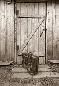 old valise near wooden door, sepia