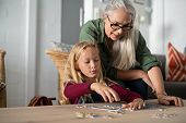 Concentrated little girl doing jigsaw puzzle with old grandmother at home. Cute little granddaughter poster