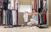 Young Woman Throwing Clothes In Walk In Closet. Mess In Wardrobe And Dressing Room poster