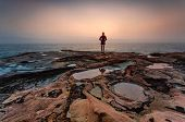 Woman Gazing Out To Sea With Foggy Coastal Sunrise And Foreground Puddles In Weathered Sandstone poster