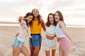 Photo of young happy smiling cheery women girls friends walking outdoors at the beach. poster