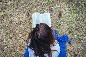 Woman Reading Book In Meadow. Lifestyle Concept. Hipster Woman Reading Book In Meadow. Leisure Lifes poster