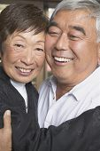 Senior Asian couple hugging and smiling