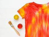 Jars Of Yellow And Red Paint And A Tie Dye T-shirt On The Table.. Flat Lay. Staining Fabric In Tie D poster