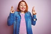 Beautiful redhead woman wearing denim shirt and striped t-shirt over isolated pink background gestur poster
