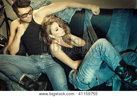 Sexy Man And Woman Dressed In Jeans Doing A Fashion Photo Shoot In A Professional Studio poster