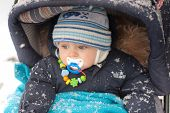 Adorable little baby boy in stroller during snowfall