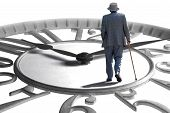 picture of father time  - A senior walking on an enlarged clock depicting aging retirement and time - JPG