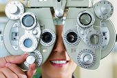 Young woman at phoropter at optician or ophthalmologist for eye test, she is near-sighted or long-si