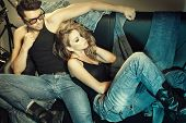 stock photo of denim jeans  - Sexy man and woman dressed in jeans doing a fashion photo shoot in a professional studio - JPG