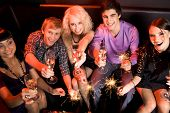 stock photo of christmas party  - Above view of joyful friends having fun at Christmas party and looking at camera - JPG