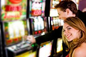 image of slot-machine  - man and woman having fun at the casino on the slot machines - JPG
