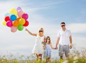 summer holidays, celebration, children and people concept - family with colorful balloons