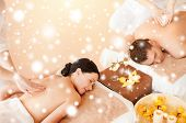 health and beauty, honeymoon and vacation concept -couple in spa salon getting massage