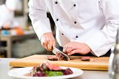 image of chef knife  - Chef in hotel or restaurant kitchen cooking - JPG
