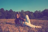 hipster girl on a summer meadow resting in grass retro colors full body shot