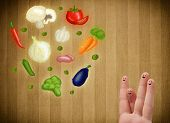 Happy smiley face fingers cheerfully looking at illustration of colorful healthy vegetables