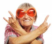 picture of retirement  - Senior woman wearing big sunglasses doing funky action isolated on white background  - JPG