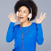 Beautiful African American woman with a fun afro hairstyle enjoying her music listening to her earph